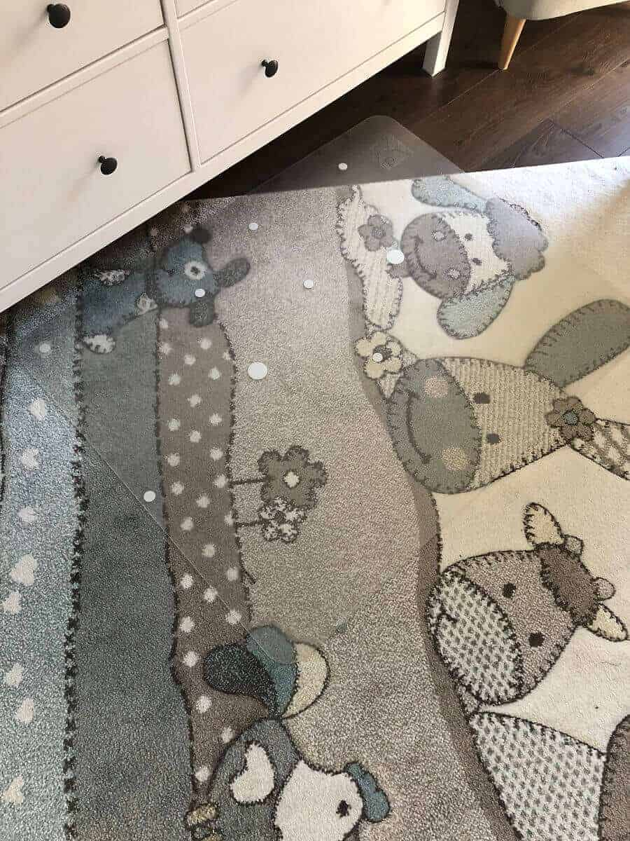 Eine Schreibtischstuhlunterlage schützt den Teppich im Babyzimmer vor Unfällen