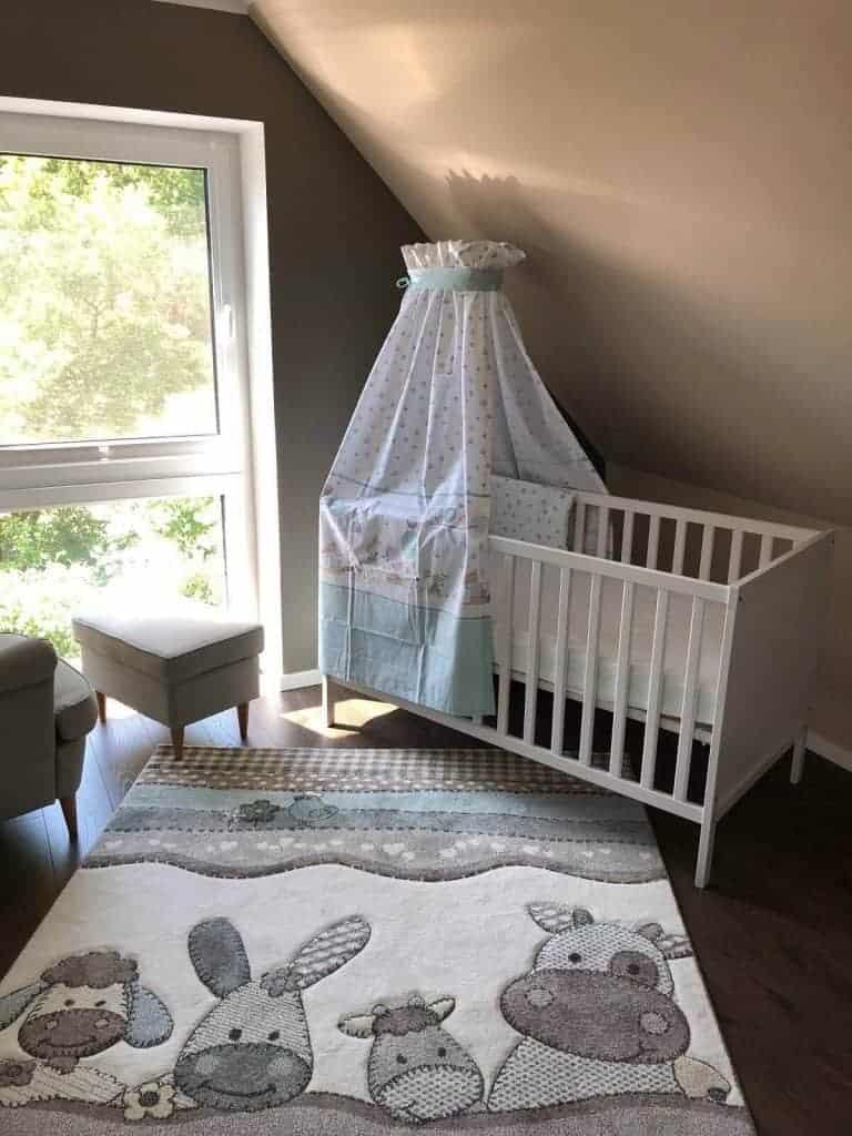 Babybett und Teppich passen super zu den Wandfarben im Babyzimmer