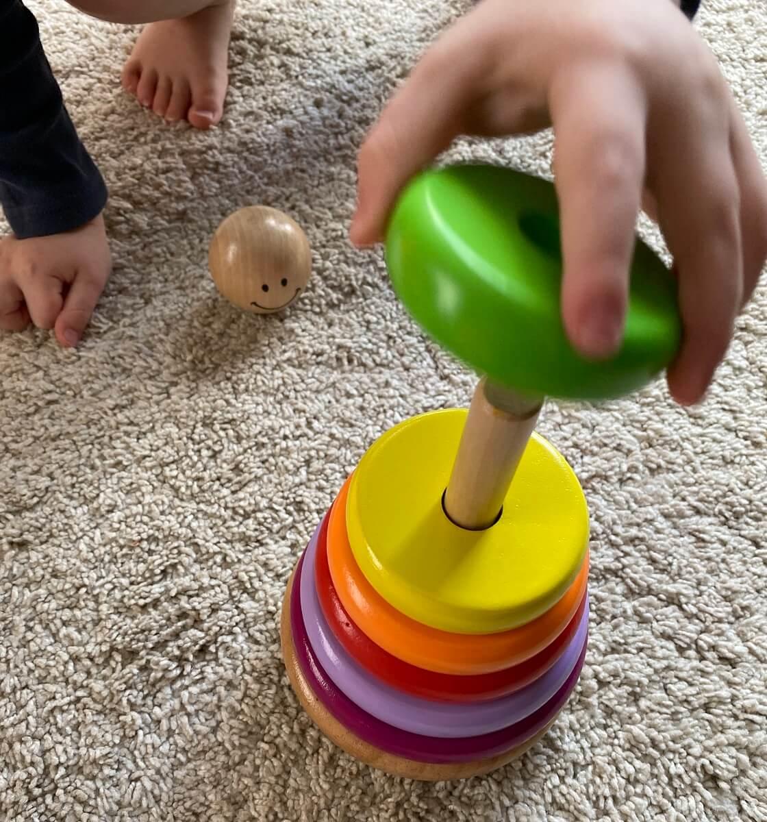 Ein Ringturm aus Holz mit verschiedenen Farben und Größen ist ein tolles Spielzeug, um die Motorik zu trainieren